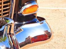 Buildings of historic downtown Sapulpa Oklahoma reflected in the chrome bumper of a restored automobile. Auto show on Route 66. stock photos