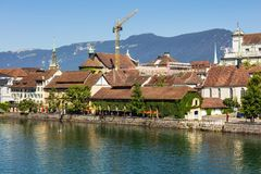 Buildings of the city of Solothurn along the Aare river. Buildings of the historic part of the city of Solothurn along the Aare river, summits of the Alps in the royalty free stock photography