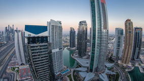 Buildings of Jumeirah Lakes Towers after sunset with traffic on the road day to night timelapse. Buildings of Jumeirah Lakes Towers after sunset with traffic on stock video