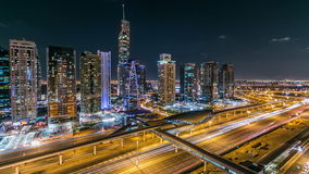Buildings of Jumeirah Lakes Towers with traffic on the road night timelapse. The JLT is a large development which consists of 79 towers being constructed along stock video footage
