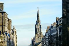 Royal Mile and the spire on the Hub in Old Town in Edinburgh. Buildings lining the Royal Mile with Scottish flags on the left and the spire on the Hub on the Royalty Free Stock Images