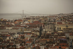 Buildings of Lisbon looking down, 25 de Abril Bridge. An image of the city of Lisbon. There`s the 25 de Abril Bridge visible in the background and a telescope Stock Photo