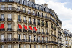 Buildings at 2nd arrondissement in Paris. Showing 19th century architectural style. Iron, ornamental balconies and plants are in the view. Red sun screens/ Royalty Free Stock Photos