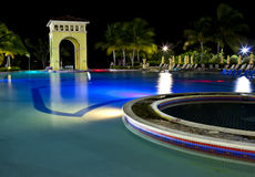 Buildings with night illumination behind pool Royalty Free Stock Photography