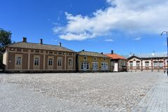 Painted buildings in different colors. Buildings of Old Rauma are painted in different colors per building like these shops in white, yellow, and light brown stock images