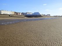 Buildings and pier on seafront and sand beach. Buildings on the seafront and the sand beach at Burnham-on-Sea in Somerset, England royalty free stock photo