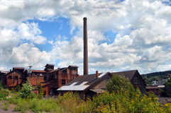 Buildings of the Quincy Copper Smelter. Historic buildings and smokestack of the derelict, Quincy Copper Smelter in Ripley, Michigan is framed by overgrowth and Royalty Free Stock Photography