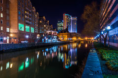 Buildings reflecting in the water at night in the Inner Harbor o Stock Images