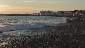 Buildings on the sea shore in sunset lights. Wide shot stock video footage