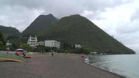 Buildings on shore of lake in mountains in province. stock video footage