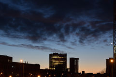 Buildings silhouettes in the city at night. Dark clouds at sunrise. Royalty Free Stock Photo