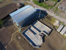 Buildings on the site. Hangar from metal profile, corrugated. The foundation of the house. Stock Photography