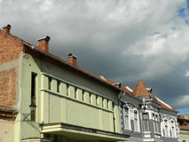 Buildings in sunlight with storm clouds incoming. City street with buildings in sunlight with storm clouds incoming Stock Photography