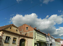 Buildings in sunlight with storm clouds incoming. City street with buildings in sunlight with storm clouds incoming Stock Image
