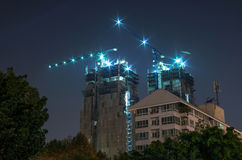 Buildings under construction with cranes and illumination Royalty Free Stock Images