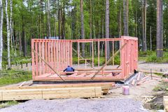 Builds a frame house, installation of the frame and walls, the beginning of construction. the concept of building a house. Worker builds a frame house royalty free stock photography