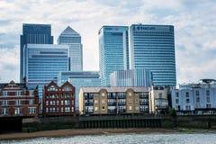 Builldings för kommersiella bankrörelsen överskuggar bostads- hem på Canary Wharf, London Arkivbild