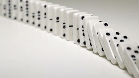 Built figure of dominoes falling in slow motion stock footage