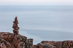 Built of stone inukshuk statue on the sea coast. Stock Image