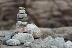 Built of stone inukshuk statue on sea coast Stock Photos