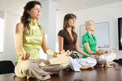Buinesswomen sitting in lotus position Stock Photo
