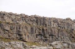 Buio e colonne morte del basalto e un funzionamento del fiume sotto loro vicino Fotografia Stock