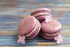 Buiscits français de macarons de myrtille avec des fleurs sur le fond en bois Image stock