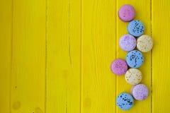 Buiscits multi français de macarons de goûts avec des fleurs sur le fond en bois Photo libre de droits