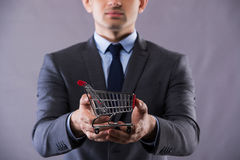 The buisinessman holding shopping cart in online shopping concept Stock Photo
