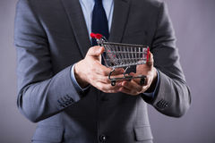 The buisinessman holding shopping cart in online shopping concept Stock Photos