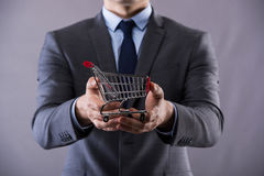 The buisinessman holding shopping cart in online shopping concept Royalty Free Stock Images