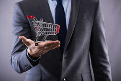 The buisinessman holding shopping cart in online shopping concept Stock Image