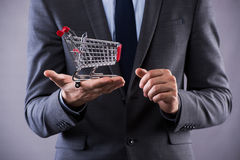 The buisinessman holding shopping cart in online shopping concept Royalty Free Stock Image