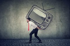 Buisness man carrying a big tv set on his back. Feeling stressed royalty free stock image