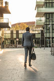 Business man walks in the new financial centre of Milan with a gym bag. Sunset Royalty Free Stock Photography