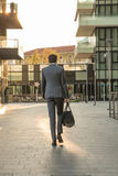 Business man walks in the new financial centre of Milan with a gym bag. Sunset Royalty Free Stock Photos