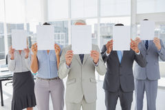Buisness team holding up blank pages and covering their faces Stock Photo