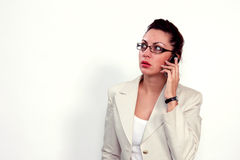Buisness woman on a cell phone. Modern female in  costume is speaking on a mobile phone Royalty Free Stock Images