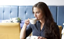 Buisness woman drinking cofee in restaurant. Portrait of beautifull buisness woman drinking cofee at restaurant. Wearing a shirt royalty free stock photo