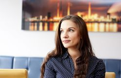 Buisness woman in restaurant. Looking at distance. Portrait of beautifull buisness woman in restaurant. Wearing a blue shirt Stock Image
