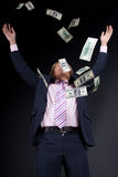 Buisnessman and falling down money Stock Photo