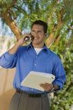 Buisnessman with folder talking on mobile phone Stock Photo