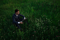 Buisnessman with laptop sit on the grass Stock Image