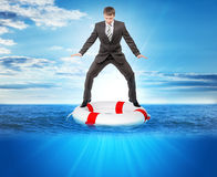 Buisnessman on lifebuoy. Looking down in sea, balance concept Stock Images