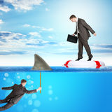 Buisnessman on lifebuoy. Looking down in sea on shark fin, business concept Stock Photography