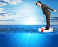Buisnessman on lifebuoy. Looking forward in sea, balance concept Royalty Free Stock Images