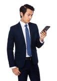 Buisnessman look at cellphone Stock Image