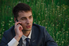 Buisnessman talk by mobile phone. At nature with flowers Stock Photo