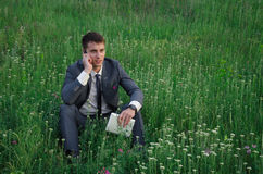 Buisnessman talk by mobile phone. At nature with laptop on the grass with flowers Royalty Free Stock Images