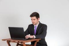 Buisnessman travaille sur un ordinateur portable Photos stock